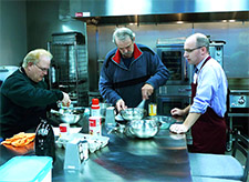 Brian Arndt, MD, (on right) prepares a meal with two participants in the Prairie Kitchen Cooking Club.