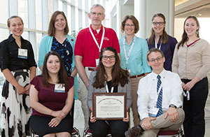David Deci, MD (in red) and FMIG students with the AAFP Program of Excellence award.