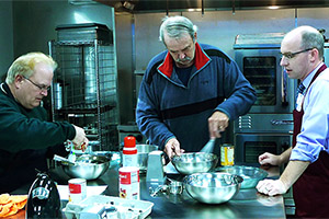 Brian Arndt, MD, (on right) prepares a meal with two participants in the Prairie Kitchen Cooking Club