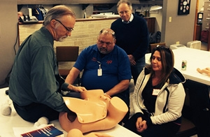 Ryan Brothers Ambulance Service medical director John Yost, MD, observes as Lou Sanner, MD, MSPH, teaches basic life support in obstetrics skills to paramedics there.