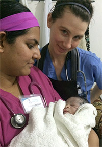Sakina Sachak, MD, and Gretchen Adams, with a newborn baby they helped deliver.